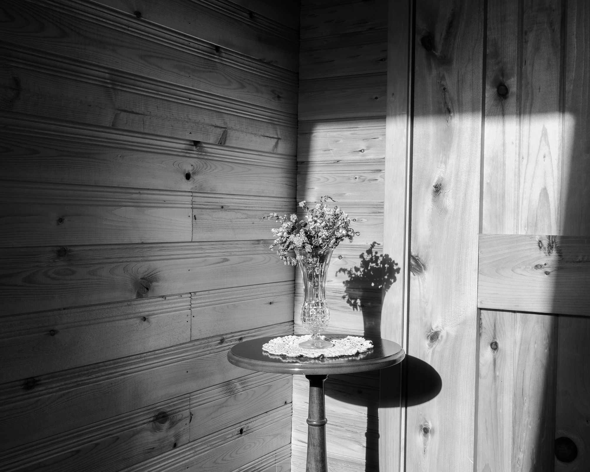 Black and White Image of the corner of a room with a flower vase on a round table.